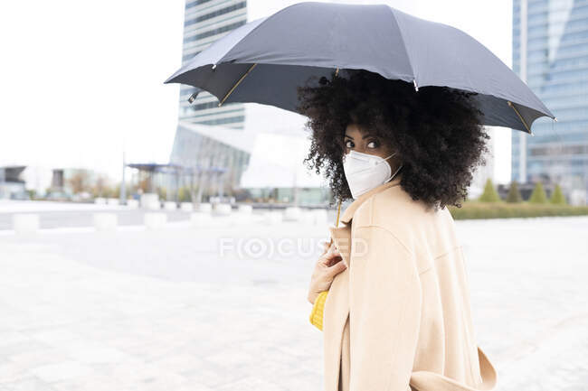 Молода жінка в захисній масці з парасолькою, стоячи надворі. — стокове фото