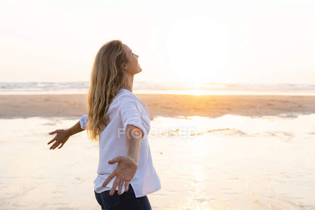 Carefree woman with arms outstretched looking up while standing against sea — Stock Photo