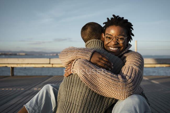Счастливая женщина обнимает друга, сидя на тропинке во время заката — стоковое фото