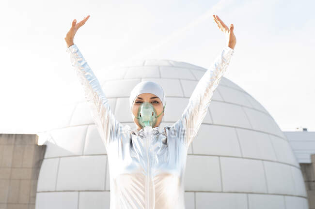 Young woman wearing protective suit and oxygen mask standing with hand raised against igloo — Stock Photo