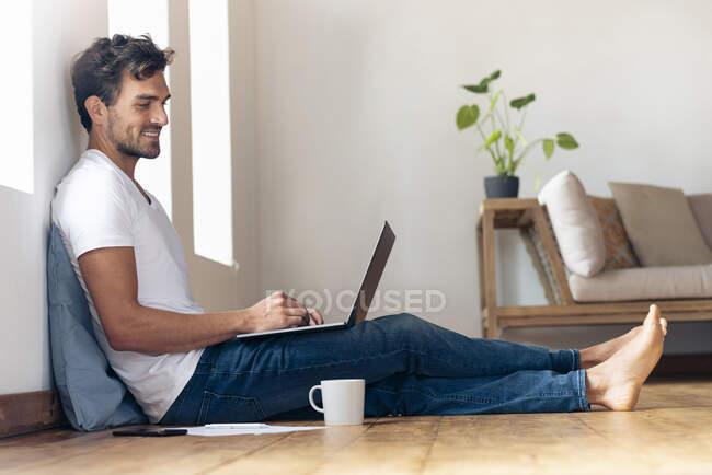 Усміхнений чоловік використовує ноутбук, сидячи вдома на підлозі. — стокове фото
