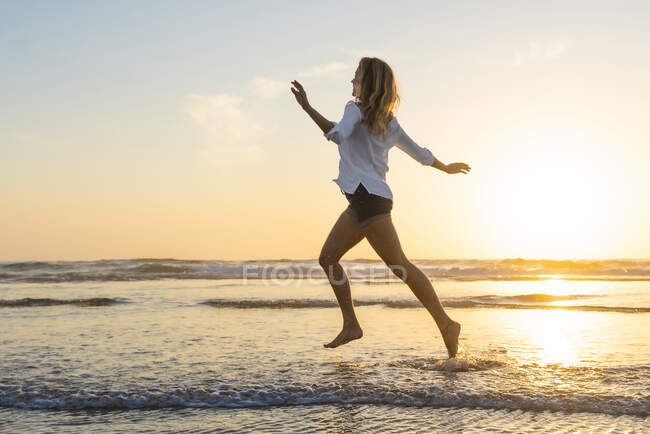 Carefree woman running with arms outstretched against sea during sunset — Stock Photo