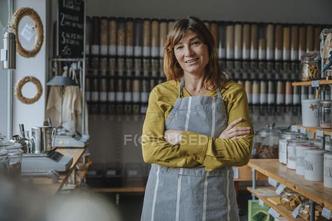 Щасливий клерк жіночої крамниці зі схрещеними руками в роздрібній крамниці. — стокове фото