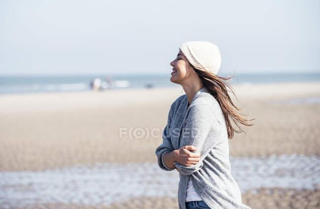 Feliz joven con sombrero de punto abrazándose mientras está de pie en la playa - foto de stock