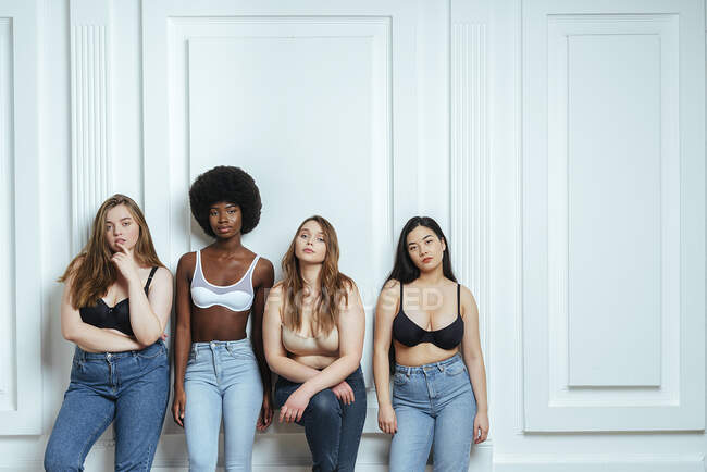 Multi-ethnic group of fashion models wearing bras and jeans posing against wall — Stock Photo