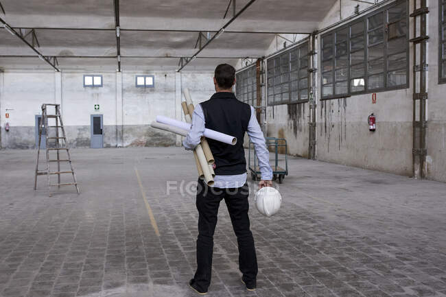Male architect holding cardboards and hardhat while standing on floor in building — Stock Photo