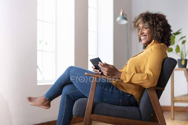 Серед дорослої жінки з цифровим планшетом, що відвернувся, сидячи вдома на стільці. — стокове фото