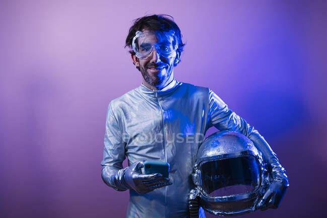 Sonriente astronauta masculino sosteniendo el teléfono inteligente y el casco espacial de color de fondo - foto de stock