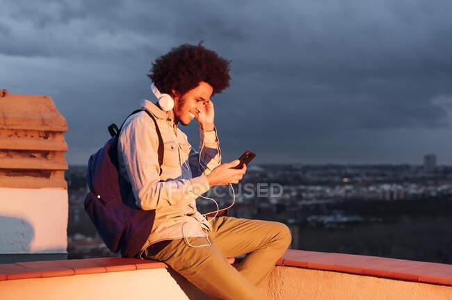 Homem sorridente ouvindo música e usando telefone inteligente no terraço contra o céu nublado ao pôr do sol — Fotografia de Stock