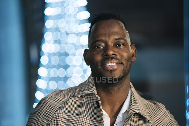 Smiling African man in coat at night — Stock Photo