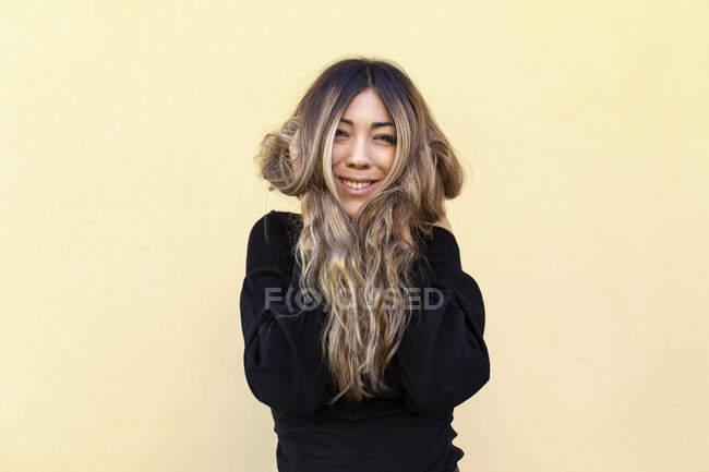 Mujer joven feliz con la mano en el pelo largo de pie sobre fondo beige - foto de stock