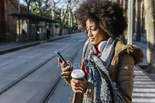 Молода жінка з чашкою кави користується мобільним телефоном, стоячи на вулиці в сонячний день. — стокове фото