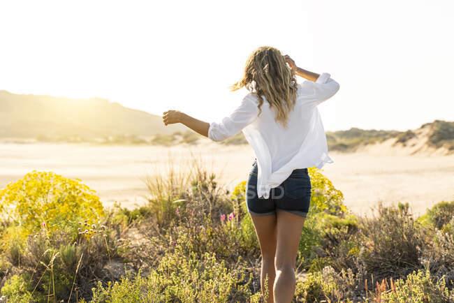 Donna che corre verso la spiaggia durante il tramonto — Foto stock