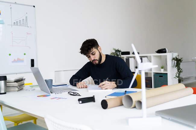 Молодий бізнесмен пише за столом у творчому кабінеті. — стокове фото