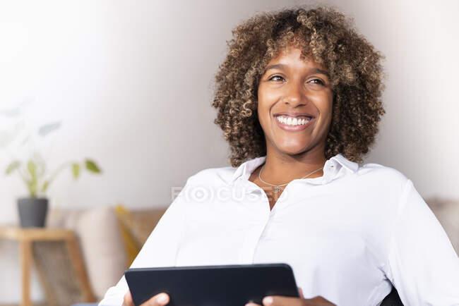 Mujer sonriente con tableta digital mirando hacia otro lado mientras está sentada en casa - foto de stock