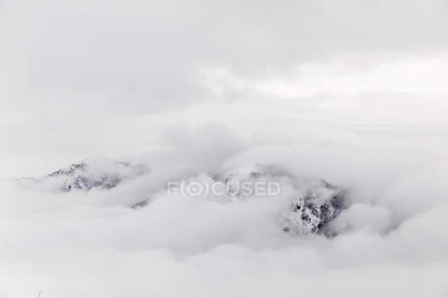 Облака, покрывающие заснеженные горы — стоковое фото