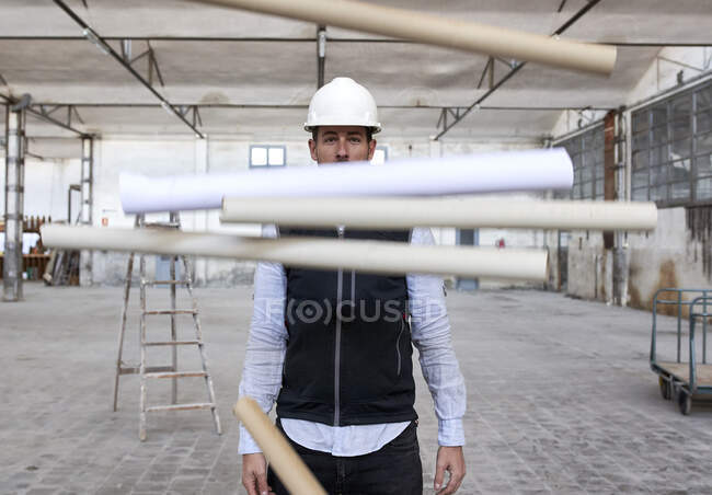 Male architect throwing cardboards while standing in building — Stock Photo
