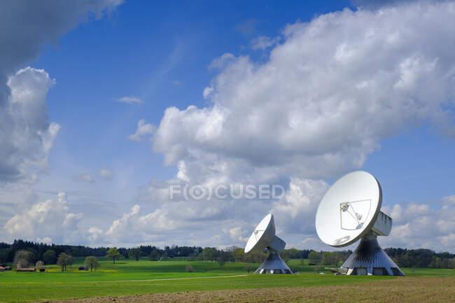 Alemania, Baviera, Raisting, Nubes sobre antenas Cassegrain de pie en el campo - foto de stock
