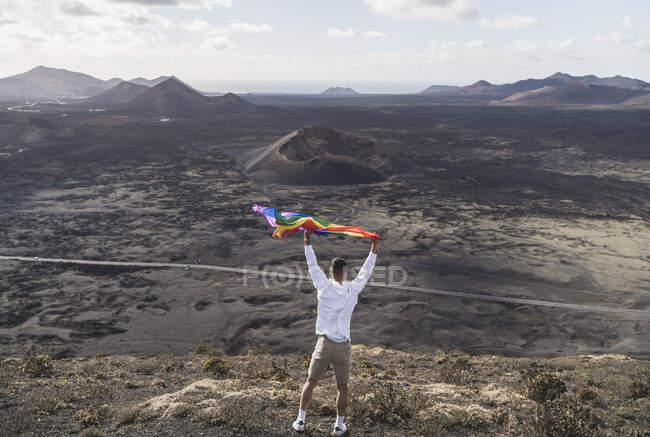 Giovane turista maschio che ondeggia arcobaleno mentre si trova al vulcano El Cuervo durante le vacanze, Lanzarote, Spagna — Foto stock
