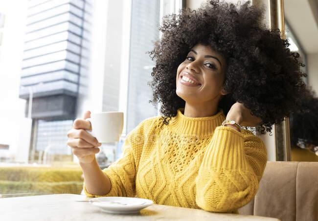 Giovane donna con mano in capelli tenendo tazza di caffè mentre seduto al caffè — Foto stock