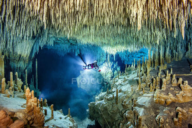 Male cave diver exploring amidst stalactite and stalagmite in sea, Cenote Uku Cusam, Quintana Roo, Mexico — Stock Photo