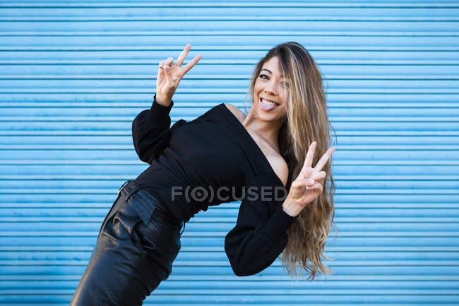 Весела жінка вистилає язик і показує знак миру проти синьої стіни. — стокове фото