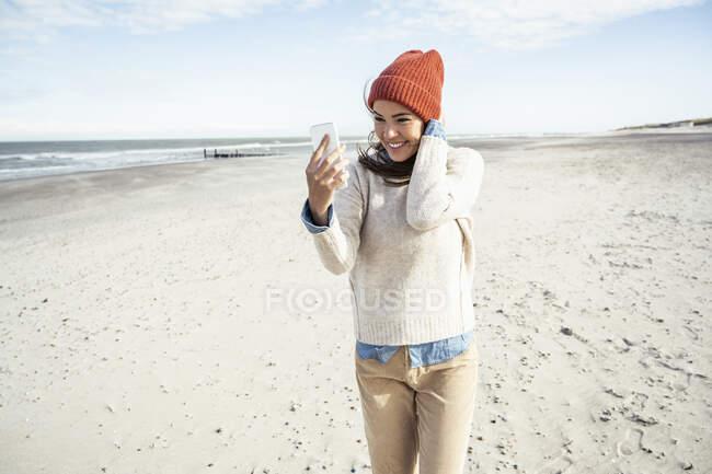 Ritratto di donna con cappello in maglia che parla su smart phone in spiaggia — Foto stock