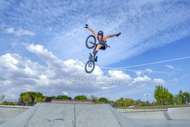 Uomo spensierato con le braccia tese saltando con la bicicletta contro il cielo blu — Foto stock