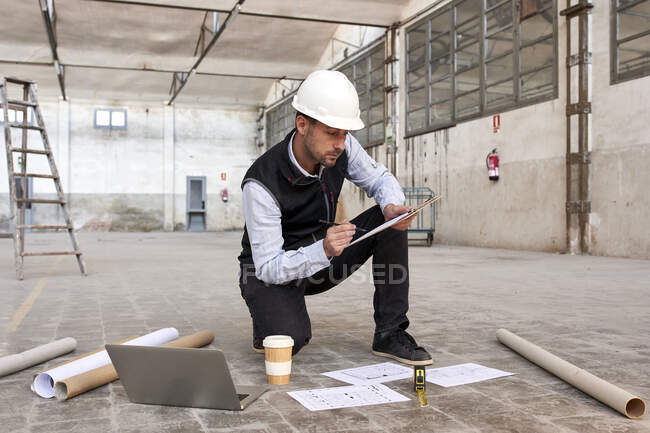 Male engineer analyzing site plan while kneeling on floor in building — Stock Photo