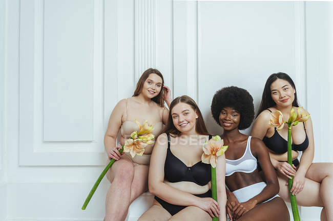 Smiling multi-ethnic group of female models in lingerie holding artificial flowers against white wall — Stock Photo