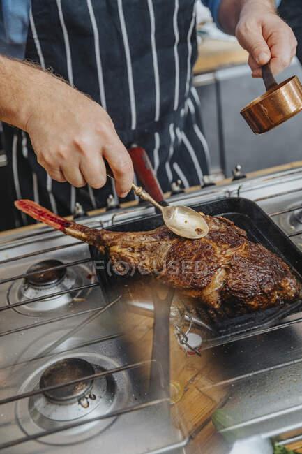 Mature chef assaisonnement tomahawk steak dans la poêle tout en restant debout dans la cuisine — Photo de stock