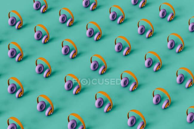 Auriculares multicolores dispuestos en una línea sobre fondo verde - foto de stock