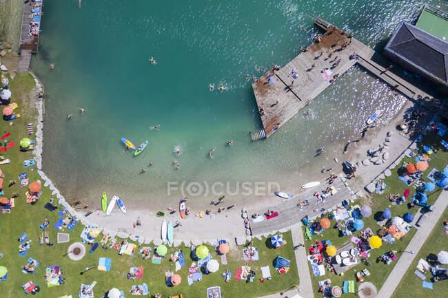 Austria, Salisburgo, Sankt Gilgen, Veduta aerea di un grande gruppo di persone prendere il sole lungo la riva sabbiosa del lago Wolfgang — Foto stock