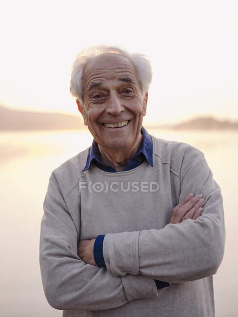 Alegre hombre mayor de pie con los brazos cruzados contra el cielo - foto de stock