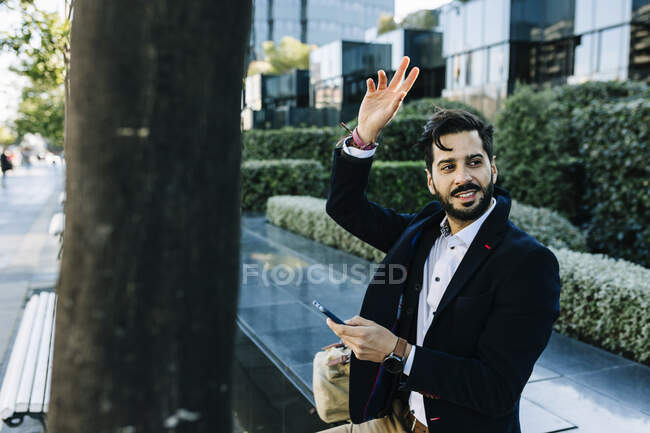 Mid adult businessman with mobile phone gesturing while sitting on bench — Stock Photo