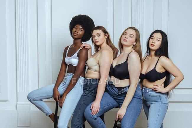 Groupe multi-ethnique de femmes portant des soutiens-gorge et des jeans contre le mur — Photo de stock