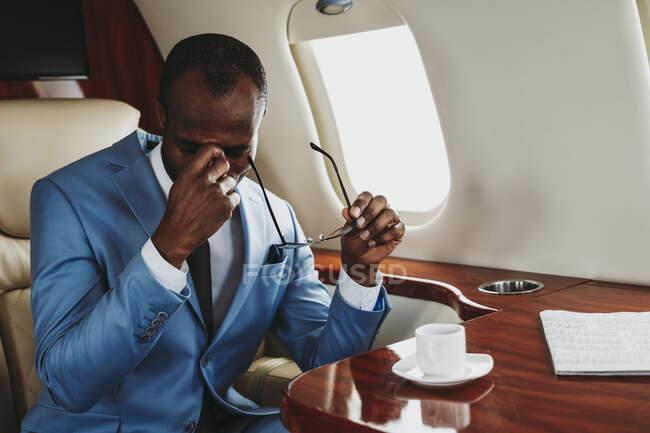 Empresario masculino preocupado sentado en jet privado - foto de stock