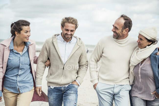 Grupo de amigos adultos caminando lado a lado a lo largo de la playa de arena — Stock Photo