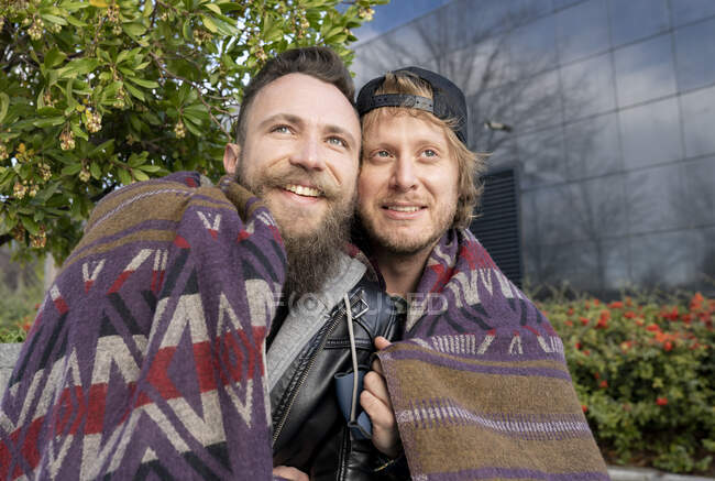 Close-up of smiling gay couple wrapped in shawl while sitting outdoors — Stock Photo