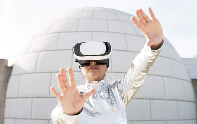 Жінка носить захисний жест костюма, використовуючи шолом віртуальної реальності проти ігло. — стокове фото
