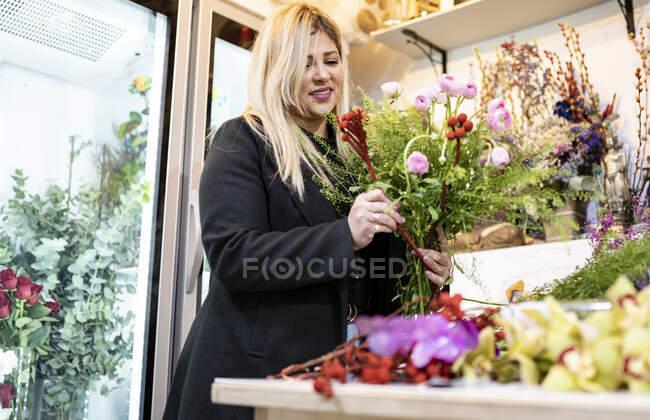 Флоріан готує букет у квітковому магазині. — стокове фото