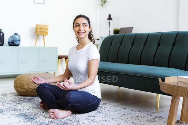 Молодая женщина улыбается, занимаясь йогой, сидя дома — стоковое фото