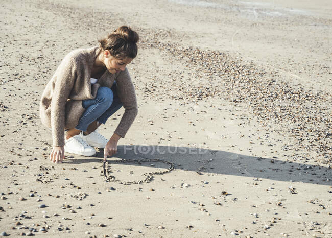 Young woman drawing heart on sand at beach — Stock Photo