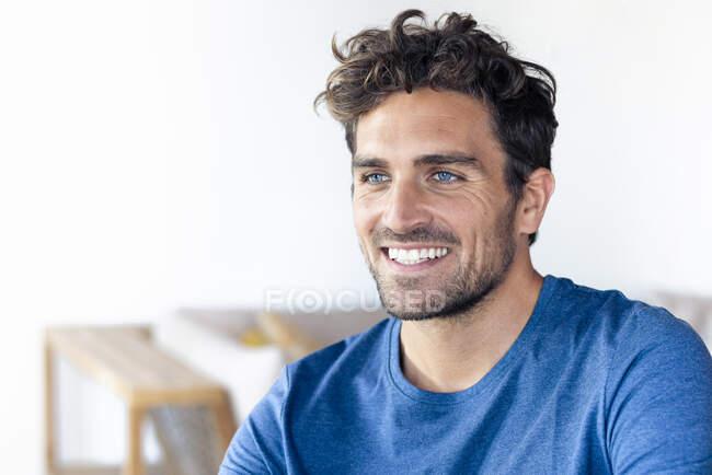 Щасливий чоловік з блакитними очима, що відвернувся, сидячи вдома. — стокове фото