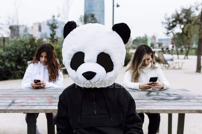 Giovane uomo con maschera panda seduto contro le amiche al parco — Foto stock