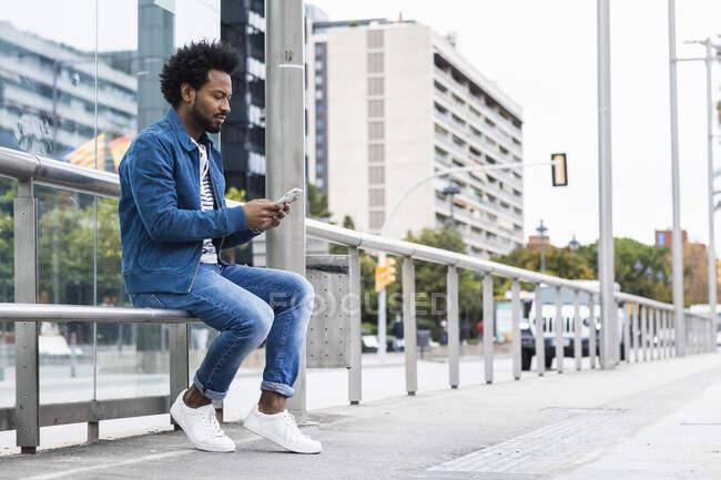 Стільний чоловік з волоссям афро за допомогою мобільного телефону, сидячи на поручнях у місті. — стокове фото