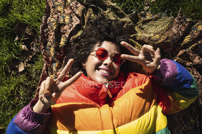 Smiling woman showing peace sign while lying on grass at park — Stock Photo