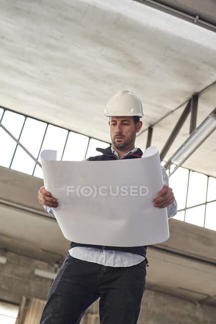Entrepreneur masculin analysant le plan du site tout en restant debout dans le bâtiment — Photo de stock