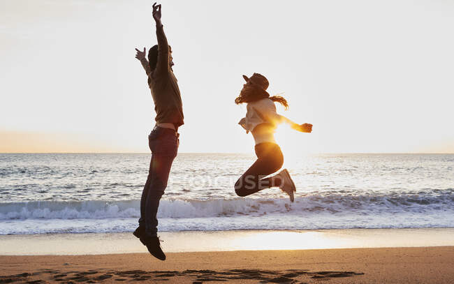 Carefree boyfriend and girlfriend enjoying while jumping against sea — Stock Photo