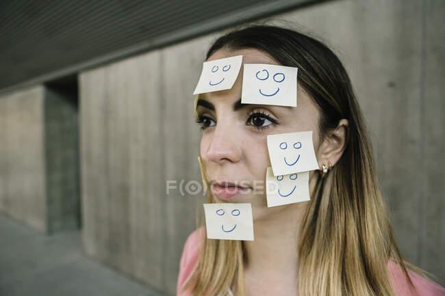 Porträt einer seriösen Frau mit Klebezetteln im Gesicht — Stockfoto